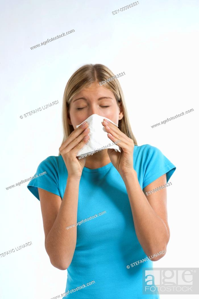 Stock Photo: Young woman blowing her nose with kleenex, isolated on white.