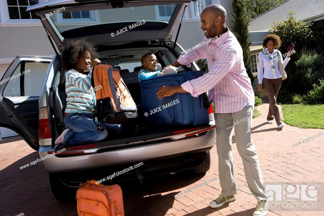 Stock Photo: Son and daughter 6-10 helping father load luggage in back of car tilt.