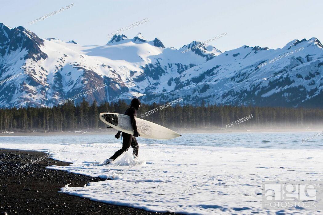 Imagen: Surfer walking into the ocean along the Kenai Peninsula Outer Coast, South-central Alaska; Alaska, United States of America.