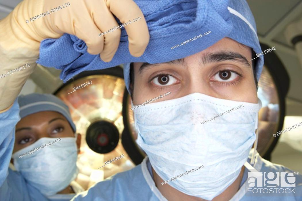 Stock Photo: Close up of Indian nurse wiping male surgeonÆs brow.