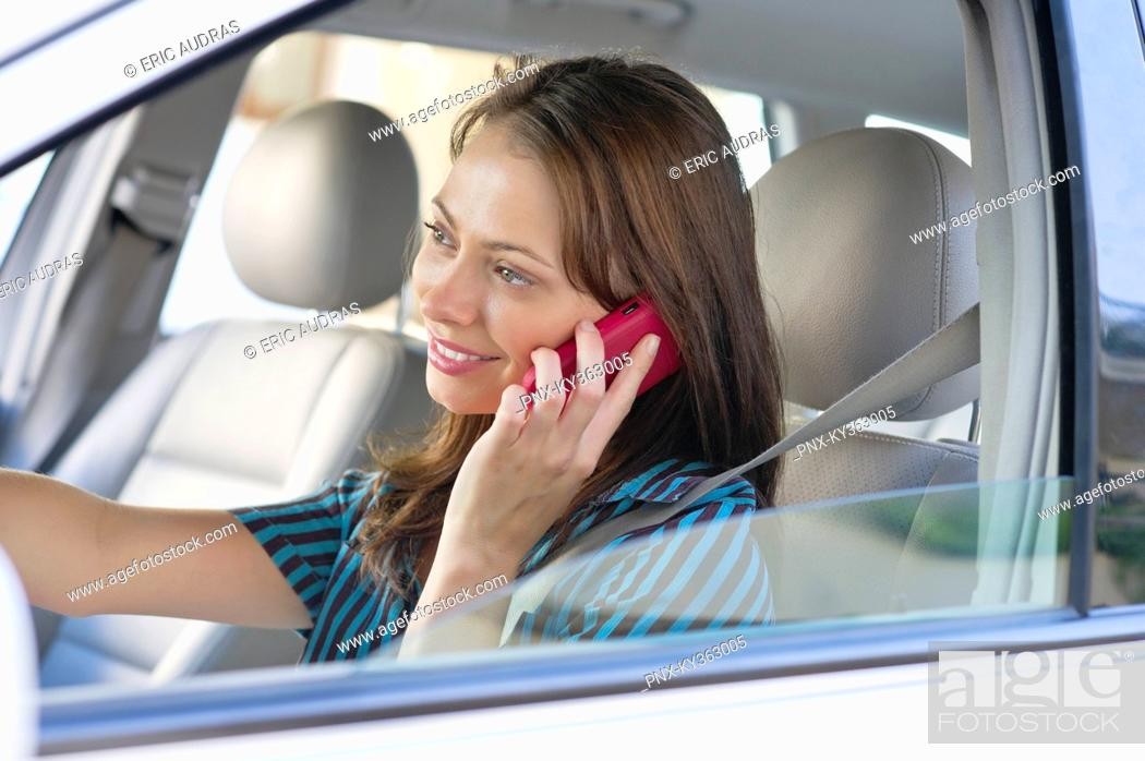Stock Photo: Beautiful young woman talking over mobile phone while driving a car.