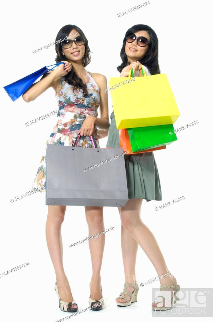 Stock Photo: Women carrying shopping bags and smiling.