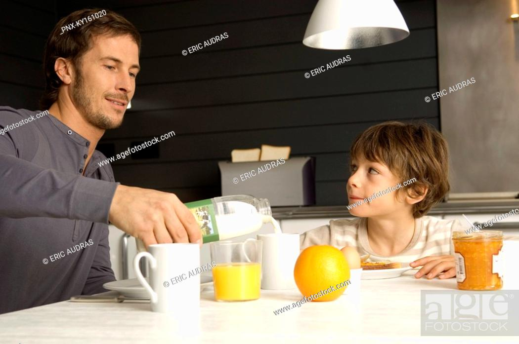 Stock Photo: Mid adult man having breakfast with his son in the kitchen.
