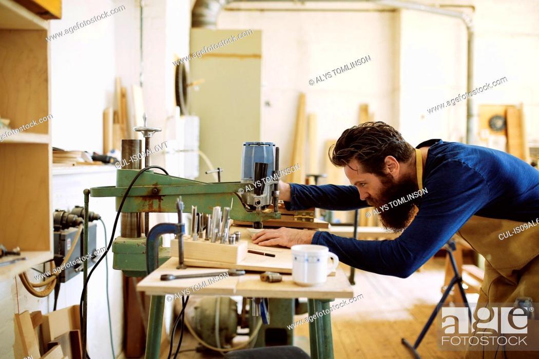 Imagen: Mid adult craftsman using machine in pipe organ workshop.