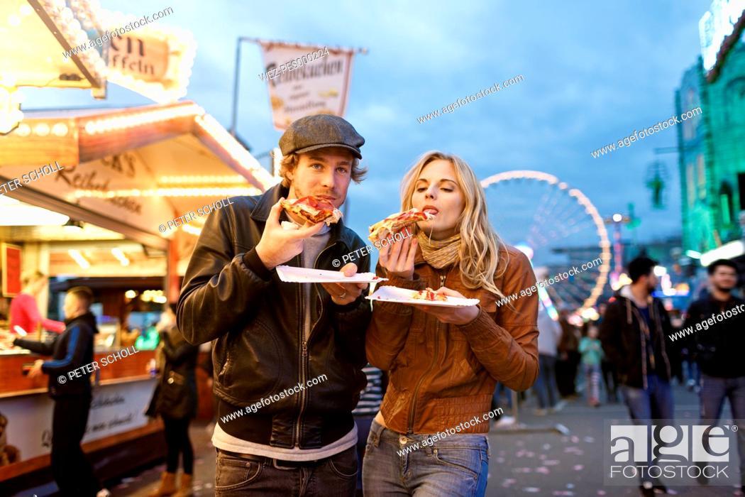 Imagen: Young couple at fun fair eating pizza.