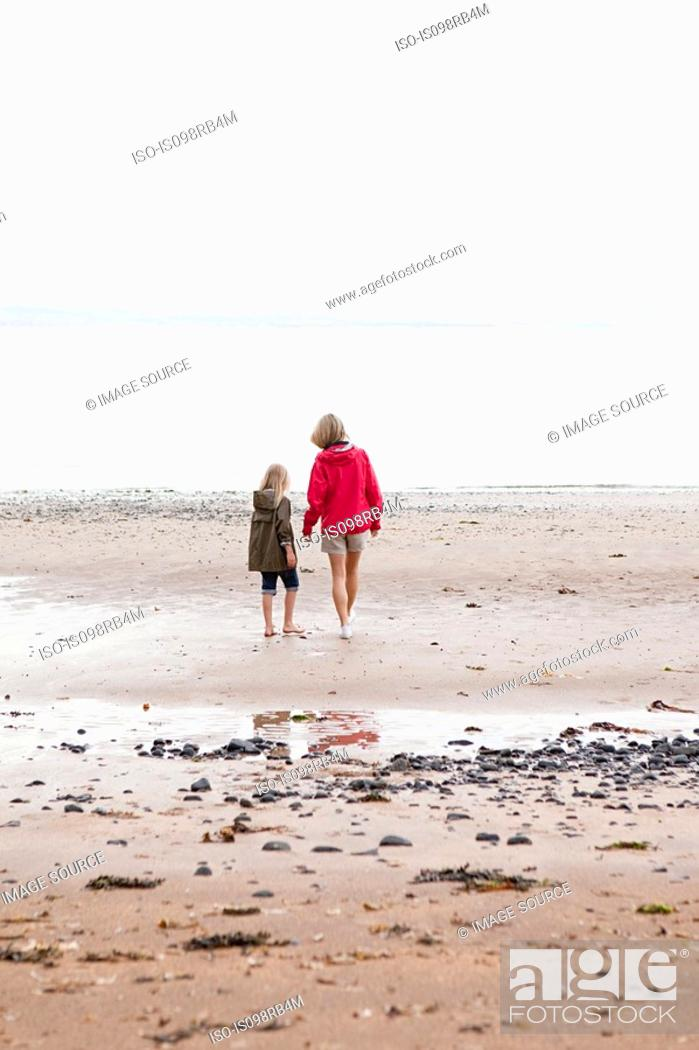 Stock Photo: Mother and daughter walking towards the sea.