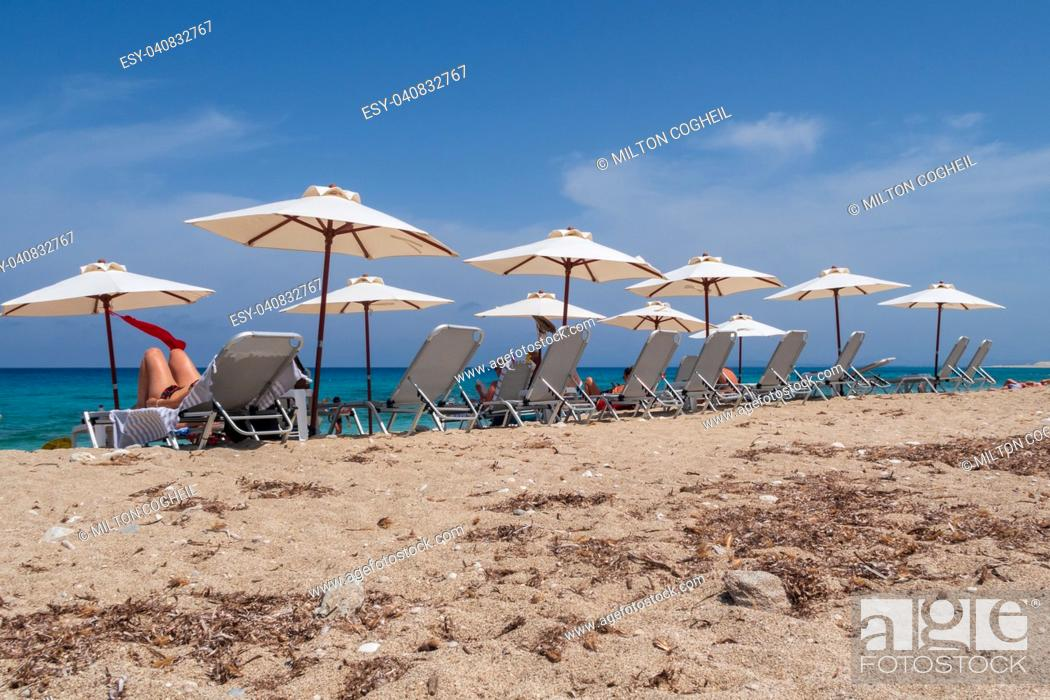 Stock Photo: Tourists relaxing on sunlounger on the beach on Lefkada island, Greece.