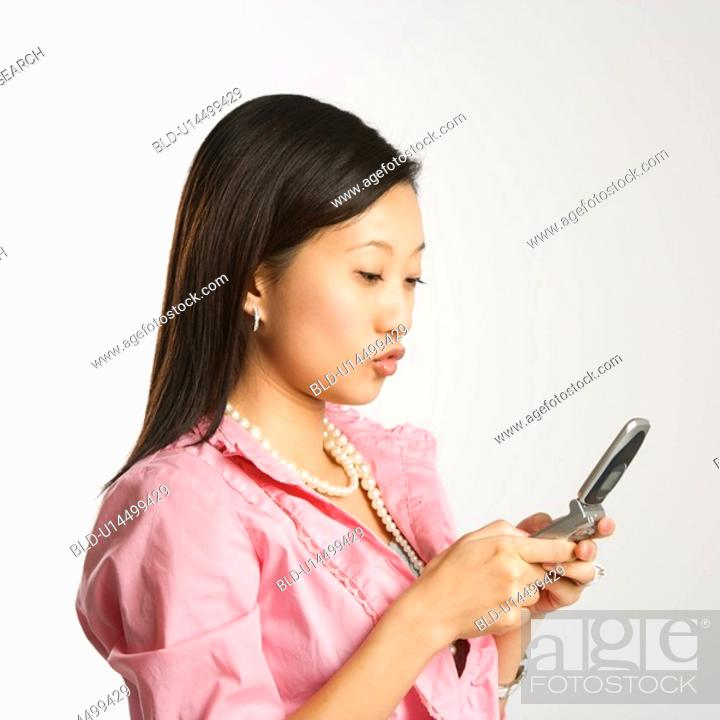 Stock Photo: Woman in business apparel texting on a cellphone.
