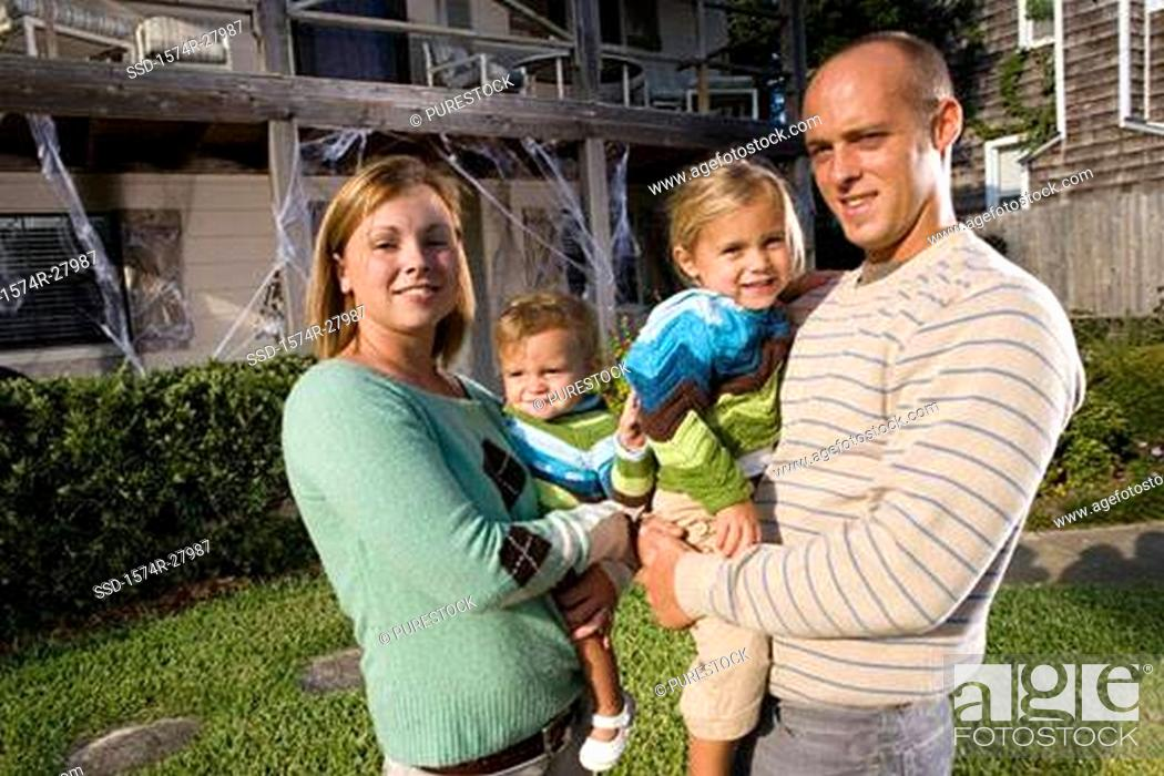 Stock Photo: Portrait of parents holding their children in front of a house.