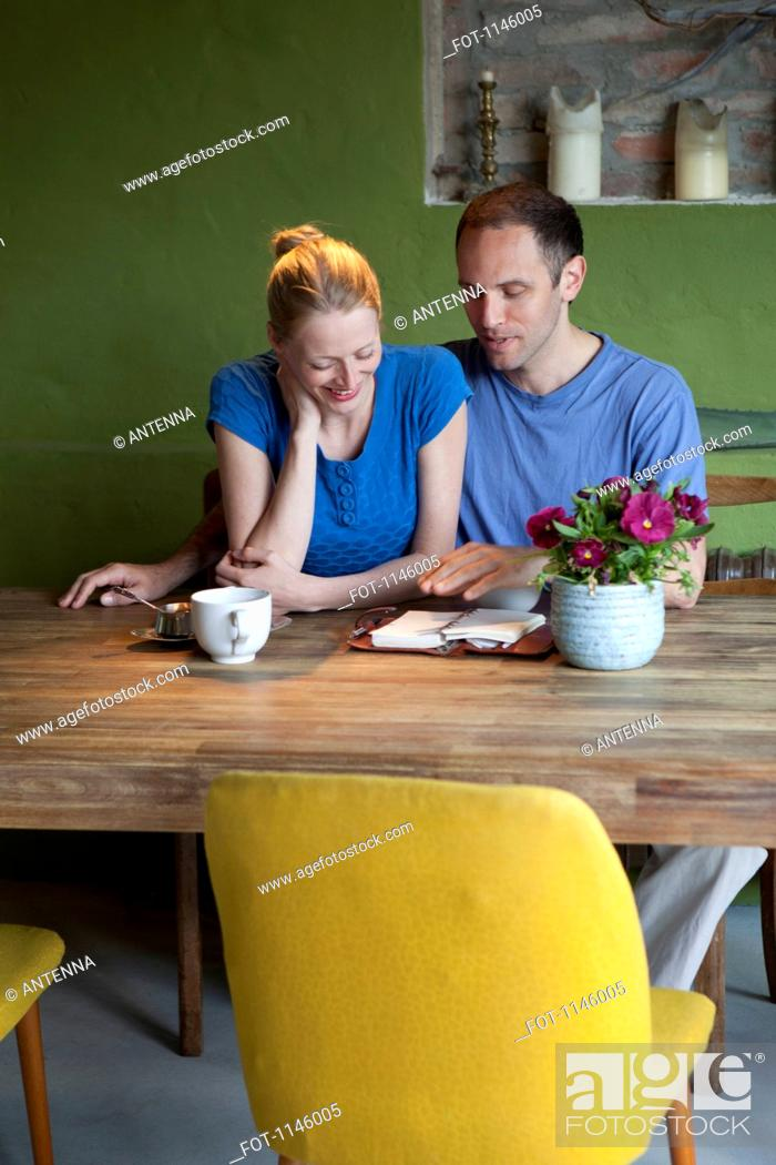 Stock Photo: A man talking about his journal to his girlfriend at the dining table.
