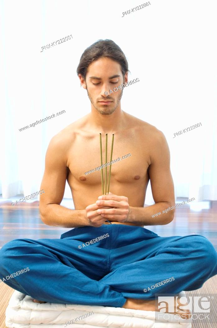 Stock Photo: Man practicing yoga and holding incense sticks.