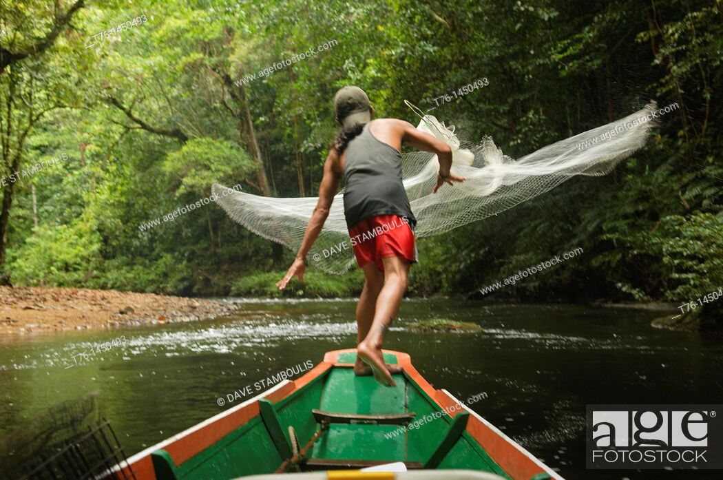 Stock Photo: Iban man casts his fishing net in Batang Ai National Park in Sarawak, Borneo, Malaysia.