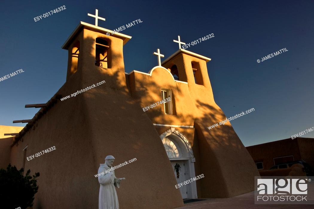 Stock Photo: The first rays of sunlight on the bell towers of historic San Fernando de Assisi church in Taos, New Mexico.