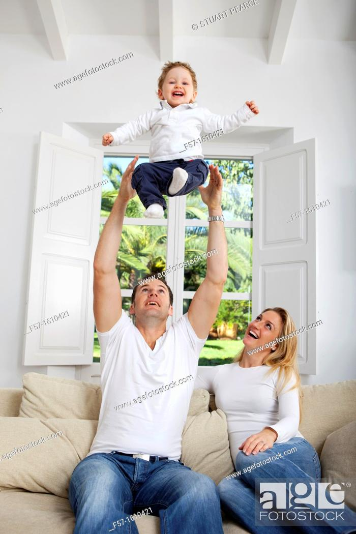 Stock Photo: Family on their sofa throwing one year old baby in the air.