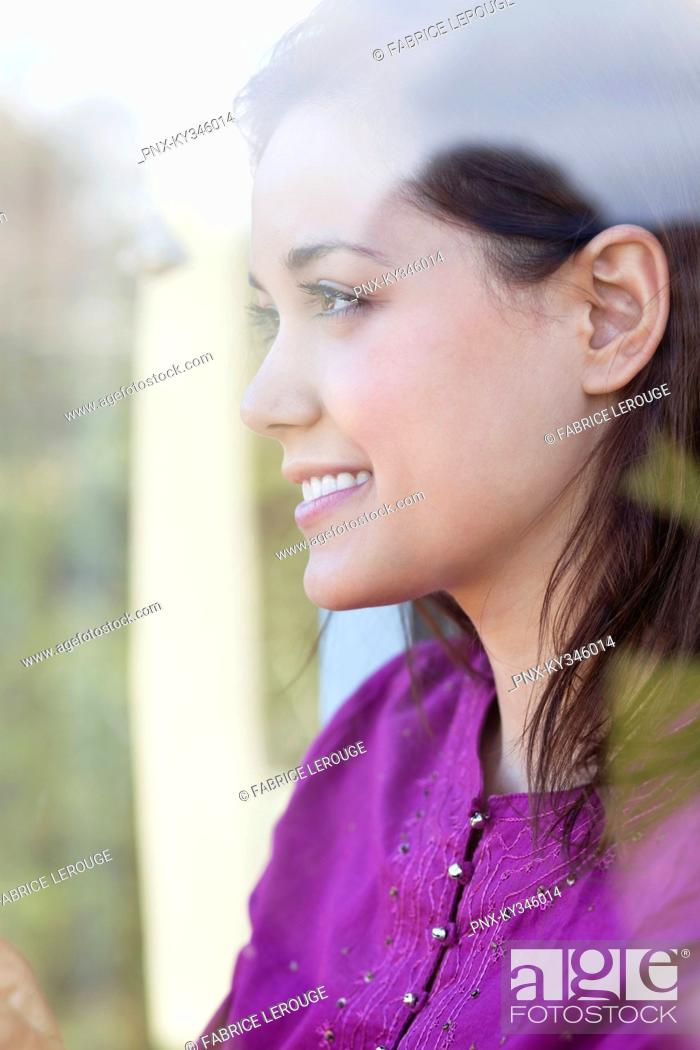 Stock Photo: Young woman looking out of the window.