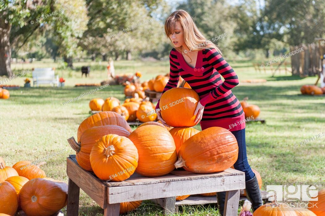 Stock Photo: 30 Year old redheaded woman with pumpkins in autumn.