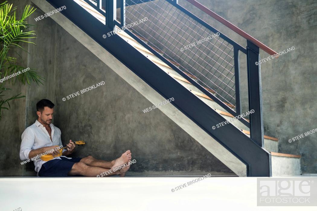 Imagen: Mature man sitting under staircase, playing the ukulele.