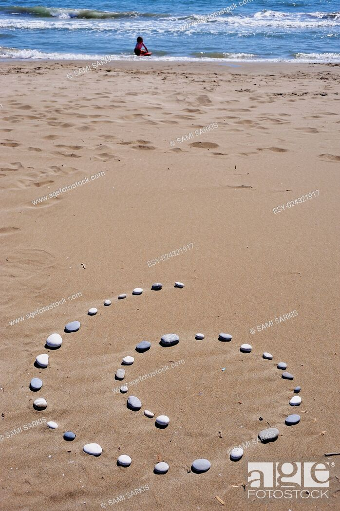 Imagen: Spiral of pebbles on beach, girl playing in the sea, Provence, France, Europe.
