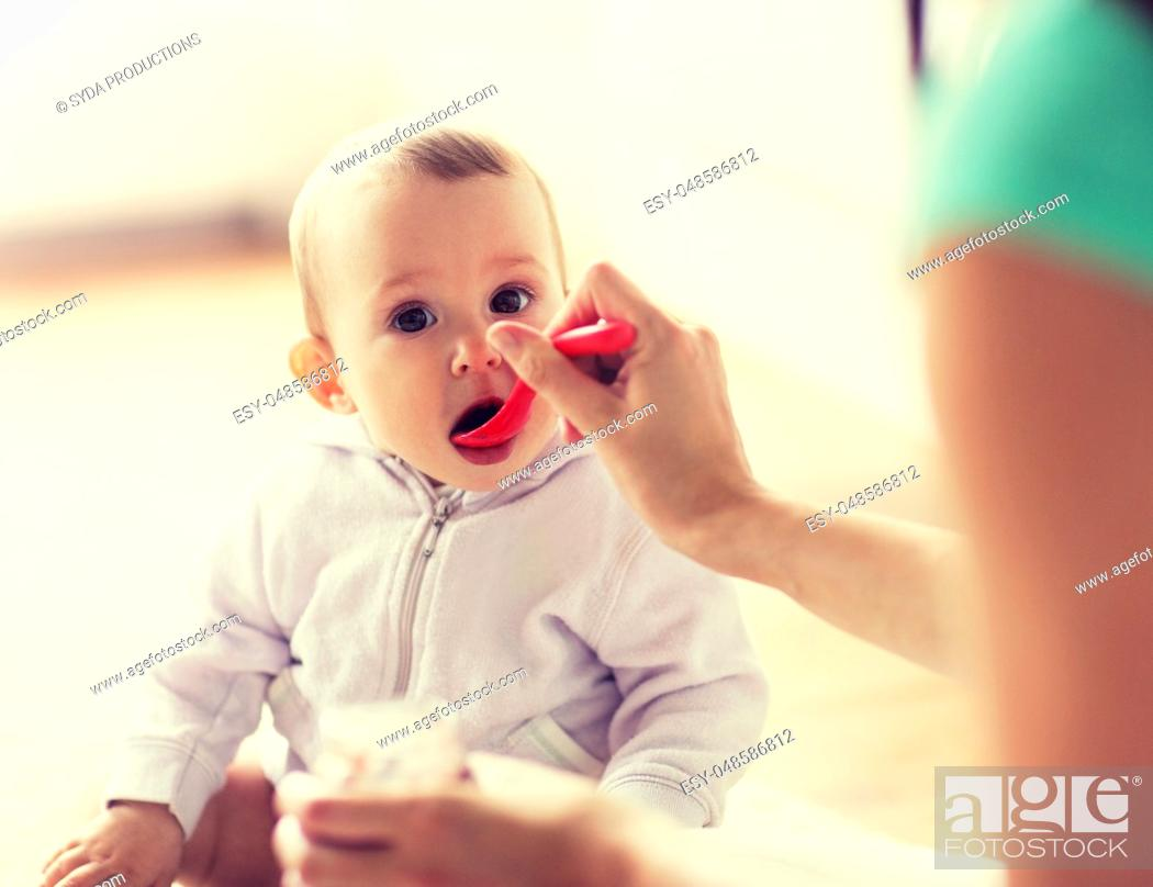 Stock Photo: mother with spoon feeding little baby at home.