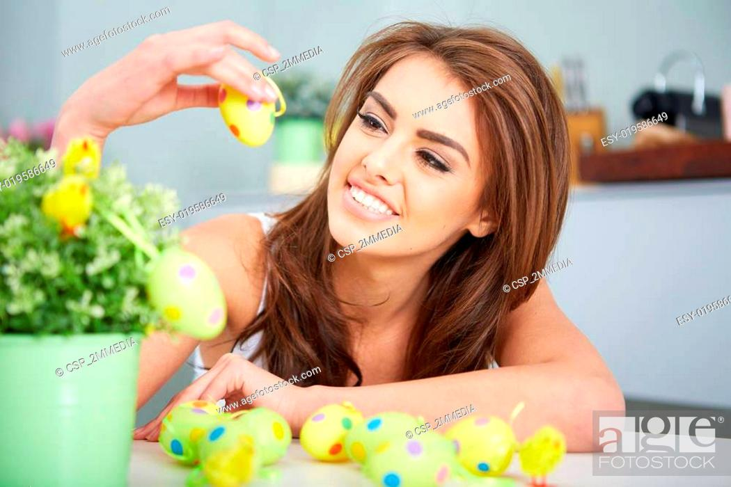Stock Photo: Smiling female laughing with colorful easter eggs.