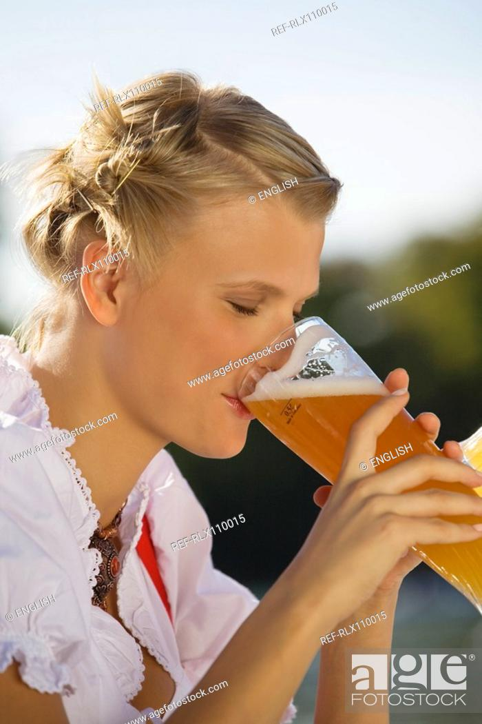 Stock Photo: Young woman in traditional Bavarian dress, drinking beer, side profile.