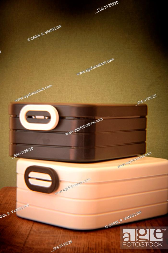 Stock Photo: Two lunch boxes sitting on wooden table. Shot with Holga lens for selective focus.