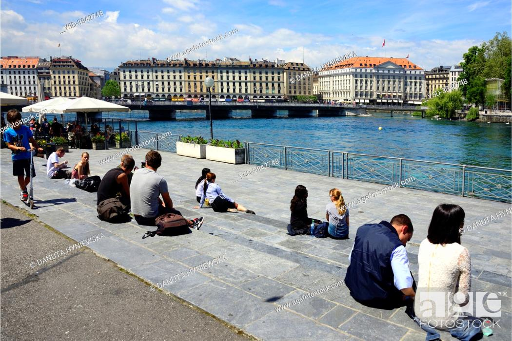 Stock Photo: People resting on terraces on bank of Rhone river, Promenade du Lac, on lef Pont des Bergues( Bergues bridge) connecting banks of river.
