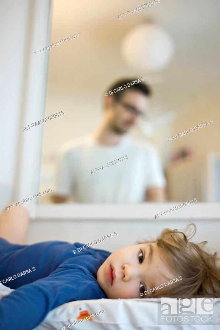 Stock Photo: Baby lying on back, reflection of father looking at baby affectionately in mirror.