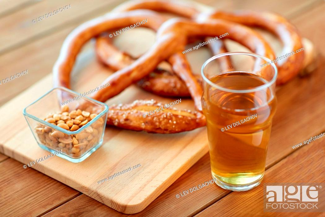 Stock Photo: food, baking, cooking and pastry concept - close up of beer in glass, pretzels and peanuts on wooden table.