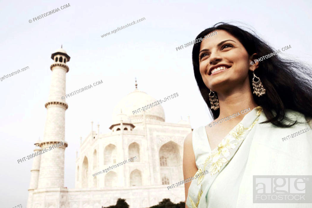 Stock Photo: Close-up of a young woman standing in front of a mausoleum, Taj Mahal, Agra, Uttar Pradesh, India.