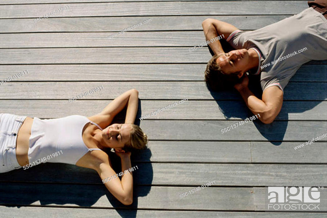 Stock Photo: High angle view of a young couple lying on wooden planks.