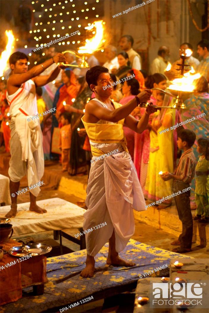 Stock Photo: Young priest performing ganga pooja at ghat on banks of holy Ganga river ; Varanasi ; Uttar Pradesh ; India.