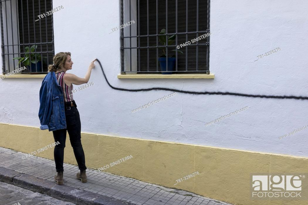 Imagen: Young woman following a line painted on a wall with her finger. Cordoba, Andalusia, Spain.