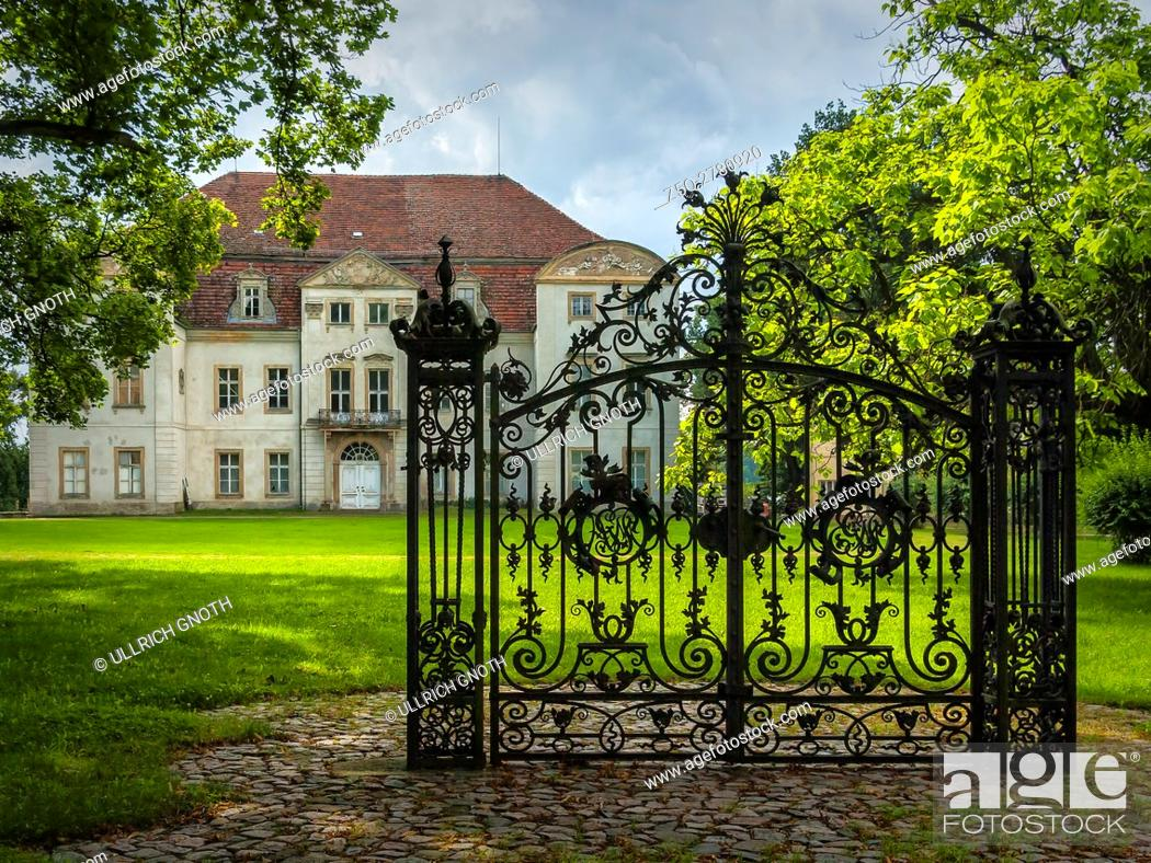 Stock Photo: An old solitary wrought-iron locked gate in front of an abandoned baroque manor house in Mecklenburg-Pomerania, Germany, standing in a park environment.