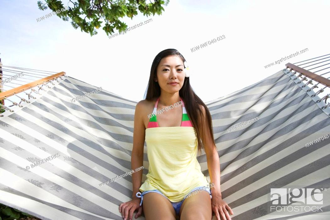 Stock Photo: Portrait of a young woman sitting on a hammock.