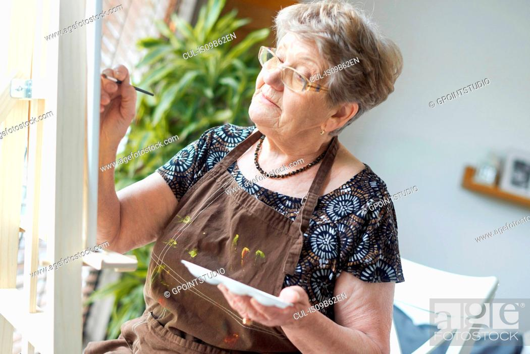 Stock Photo: Senior adult woman painting on easel.
