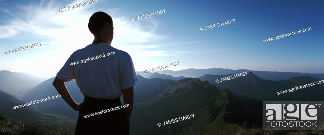 Stock Photo: France, woman looking out over mountains at sunrise, rear view, panorama.