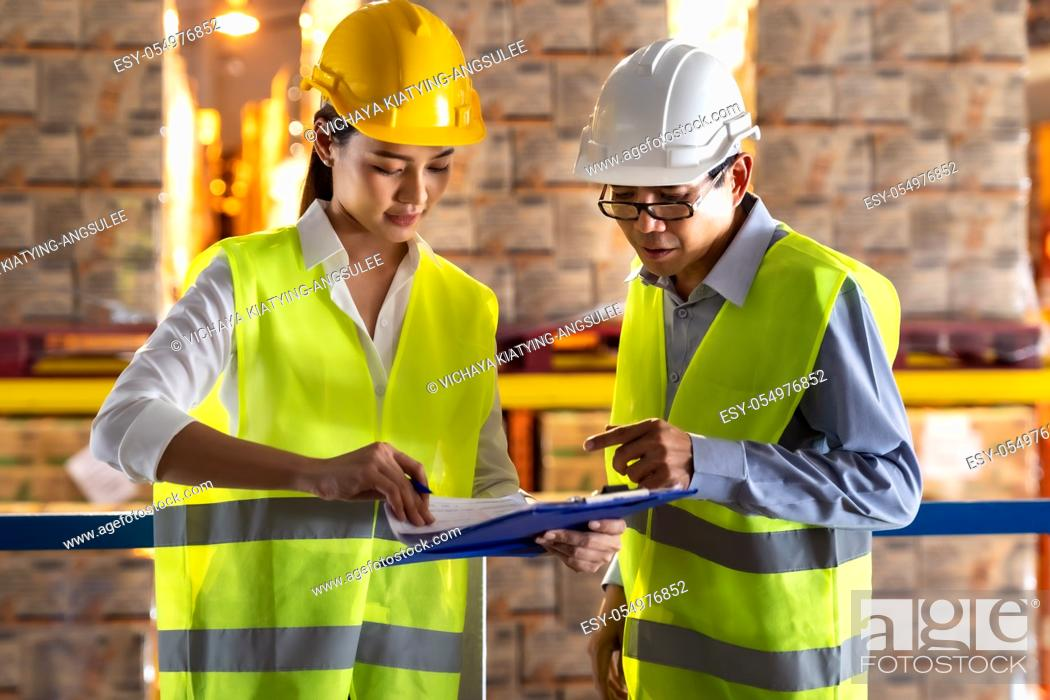 Stock Photo: Asian warehouse manager discuss with warehouse worker using archboard to assign job with distribution warehouse in background.