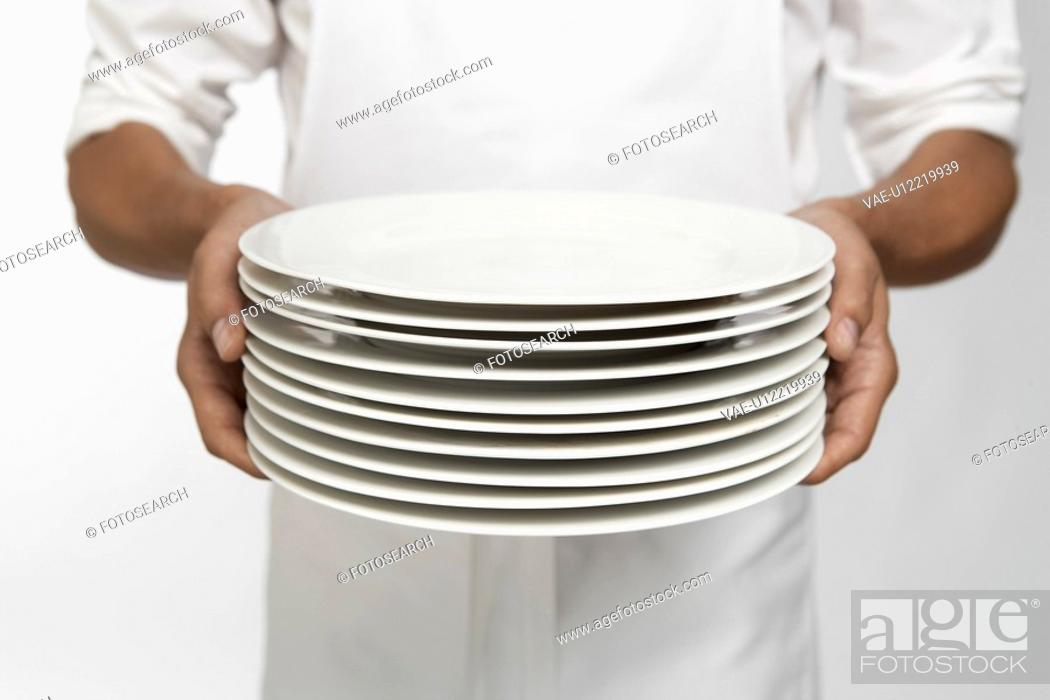 Stock Photo: Chef holding stack of dinner plates mid section.