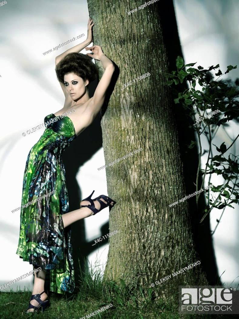 Stock Photo: High fashion photo of a beautiful woman in elegant dress leaning against a tree trunk.