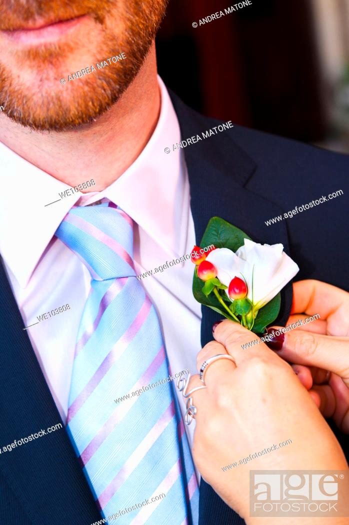 Stock Photo: Groom being helped with the buttonhole flower on lapel.