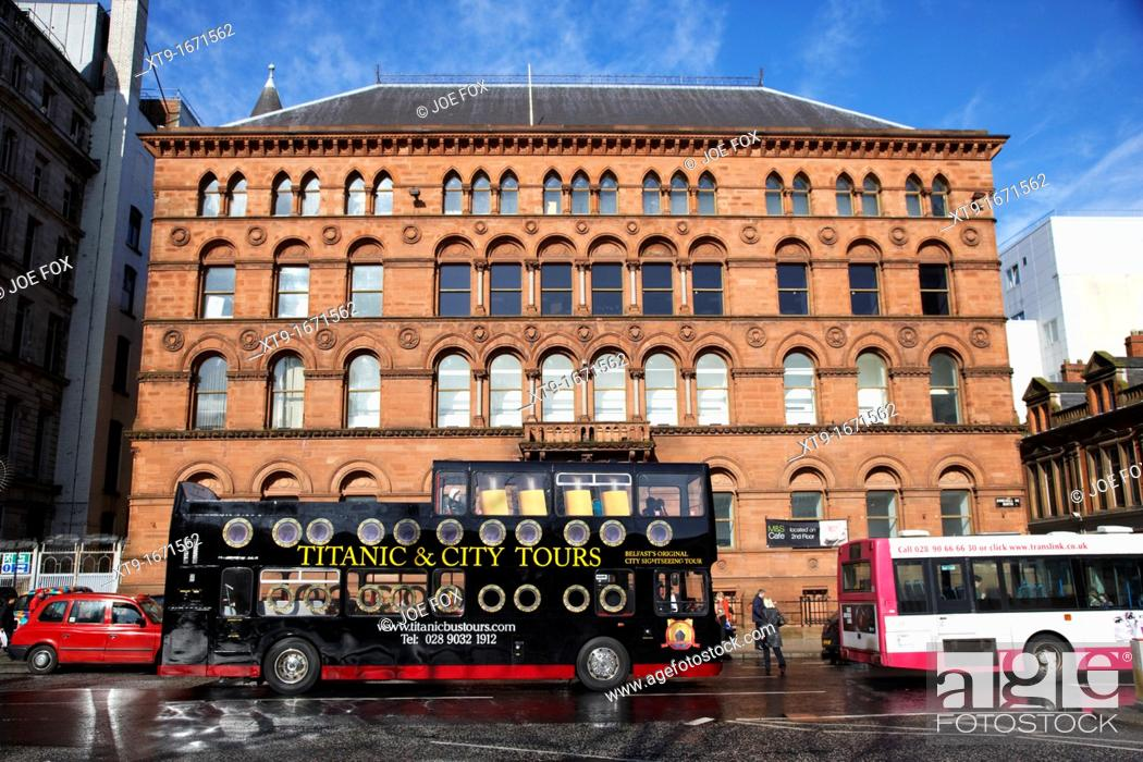 Stock Photo: titanic and city open bus tours going past old richardson owden warehouse building donegall square north Belfast city centre Northern Ireland UK.