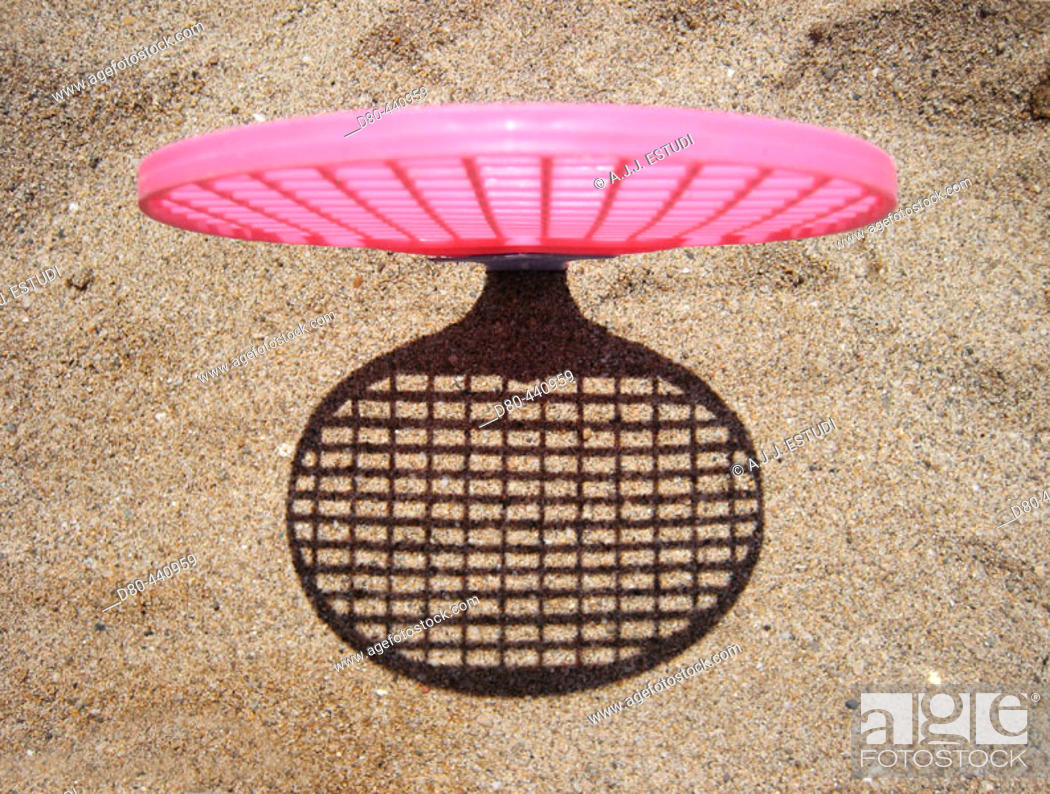Stock Photo: Racquet on sand and shadow.
