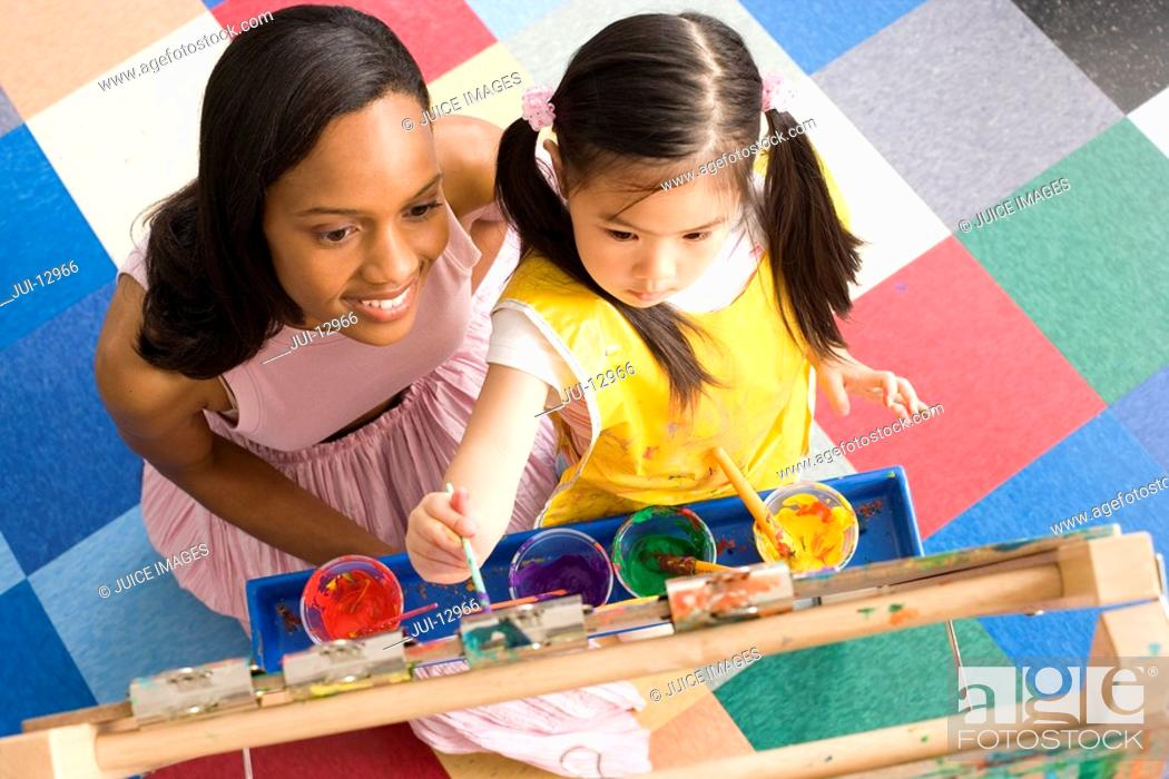 Stock Photo: Teacher by girl 5-7 using easel to paint, elevated view.
