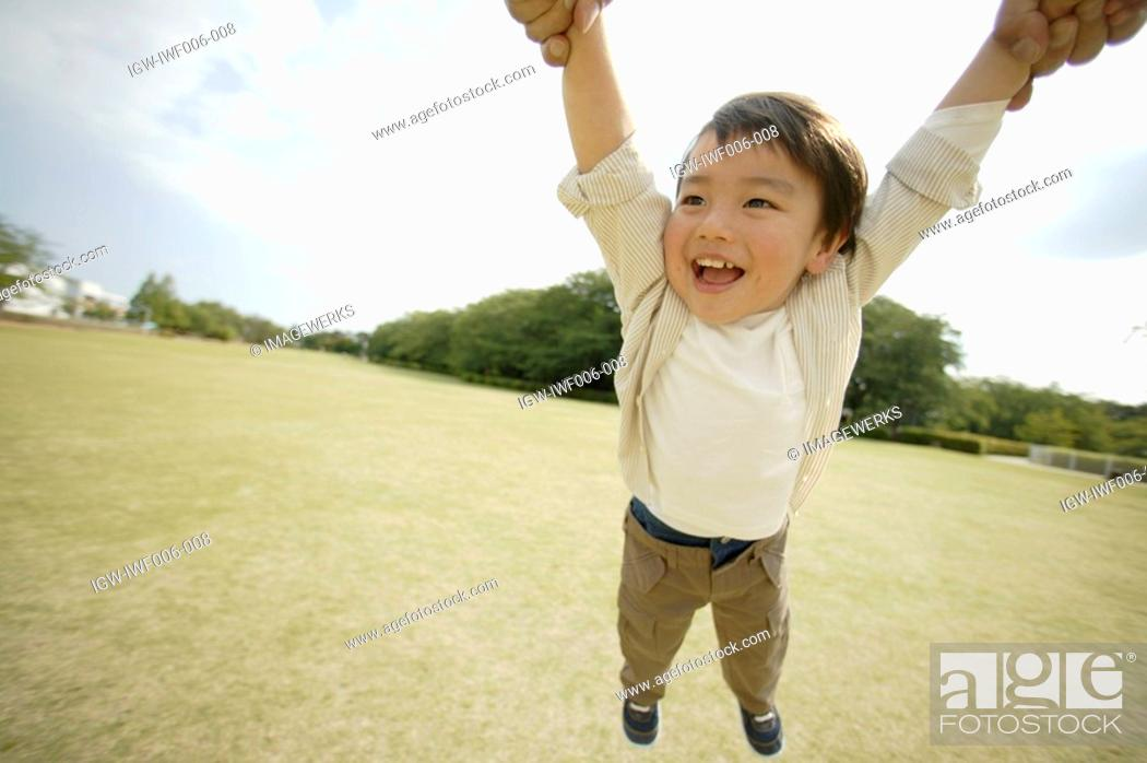 Stock Photo: A small boy is being lifted in mid air.