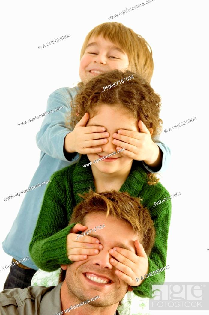 Stock Photo: Girl covering eyes of her father and her eyes covered by her brother.