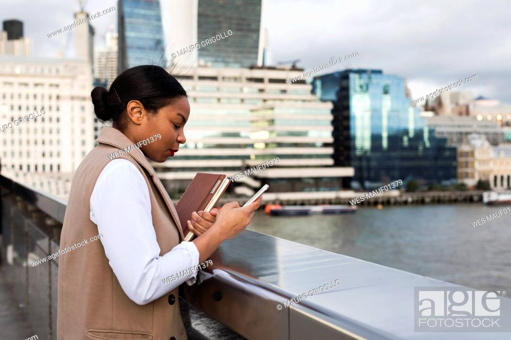 Stock Photo: UK, London, businesswoman standing on bridge using cell phone.