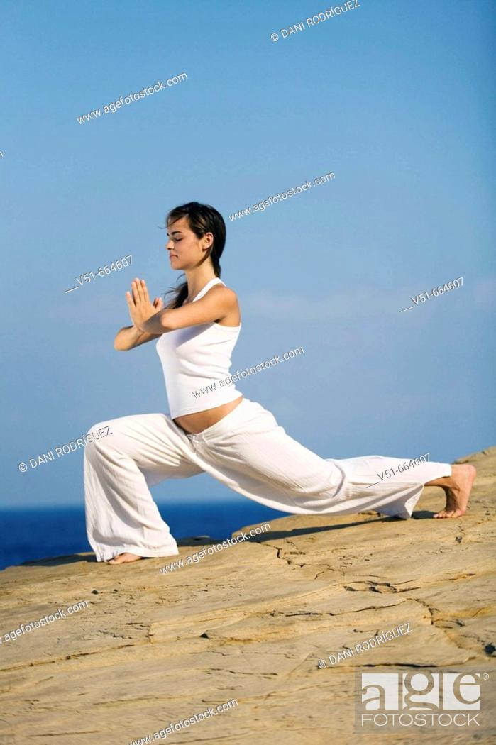 Stock Photo: Young woman practicing yoga by the sea.