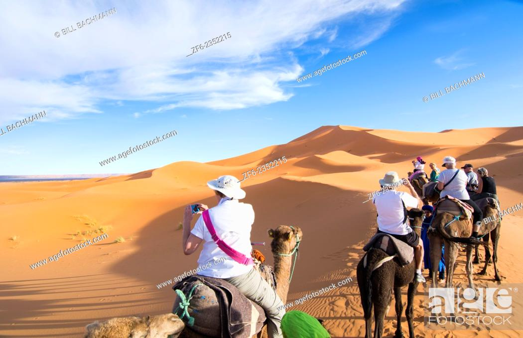 Stock Photo: Morocco Sahara Desert sand dunes in Las Palmeras area with tourists riding camels on peaks and sand.