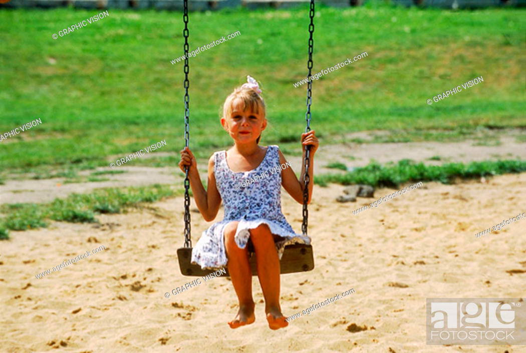 Stock Photo: Portrait of a young girl sitting on a swing.